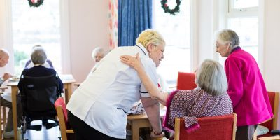 westlands-care-home-carer-with-clients-in-dining-rooom
